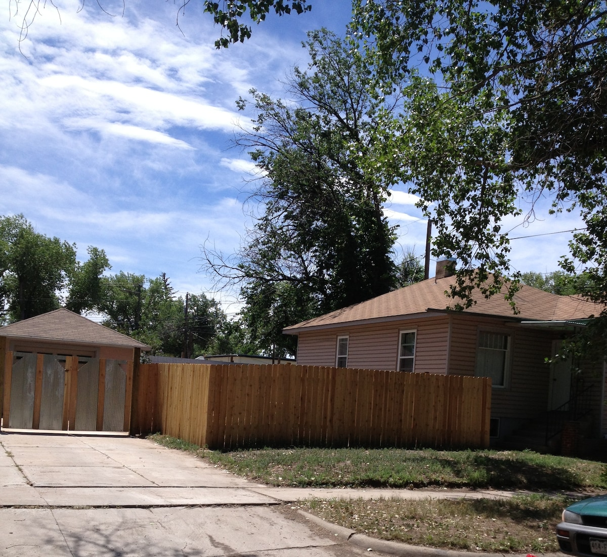 View of house/yard/driveway from the street.  Newly fenced yard with 2 gardens and outdoor furniture.