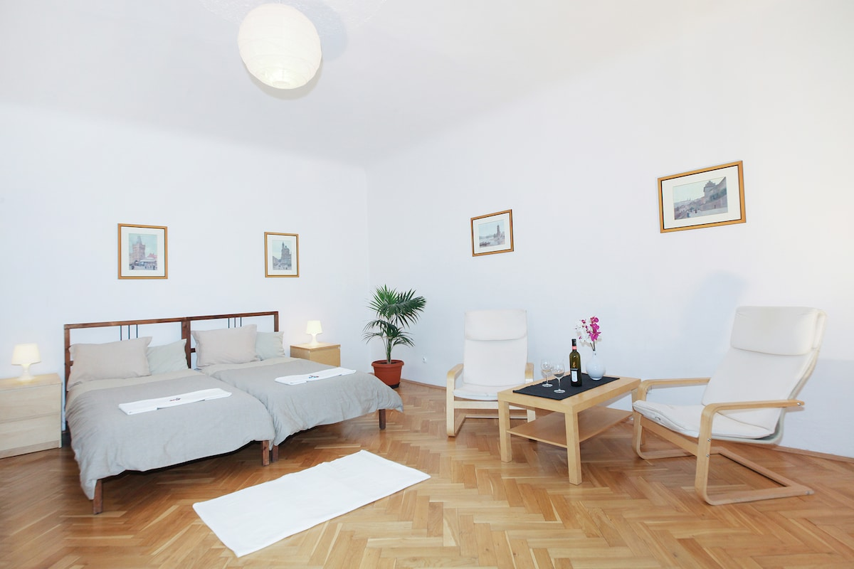 Spacious bedroom with a double bed and two comfy chairs