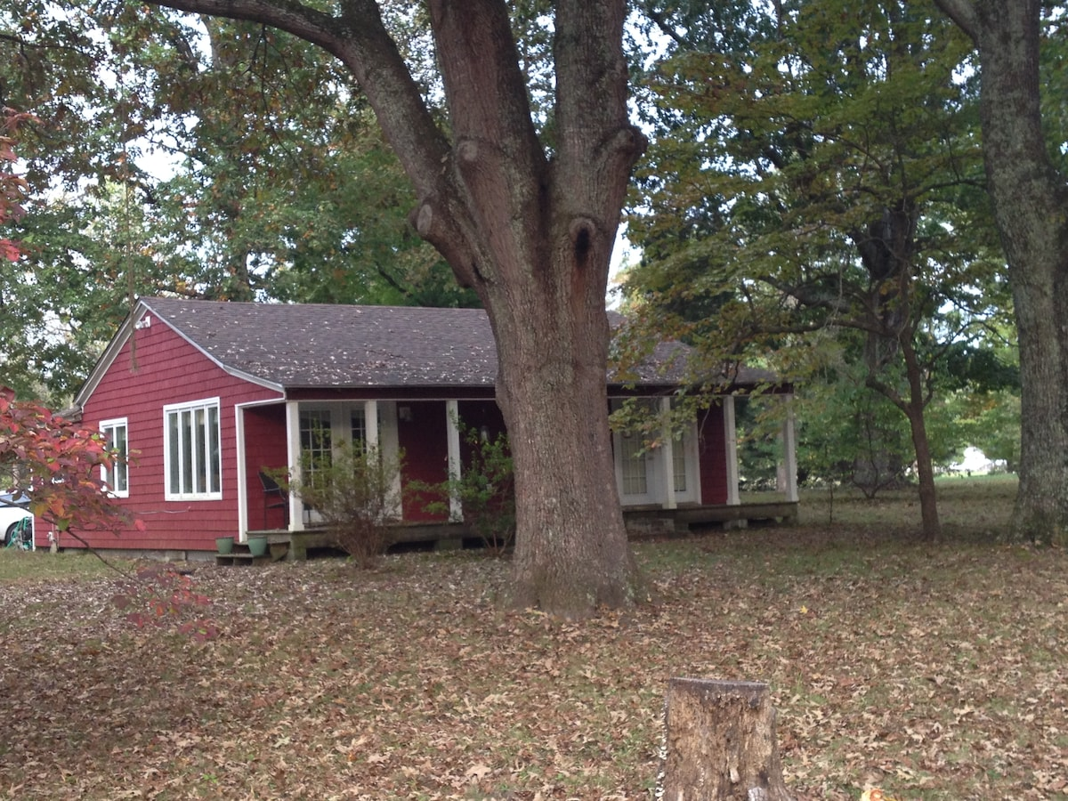 The front of the cottage. Full porch with seating.