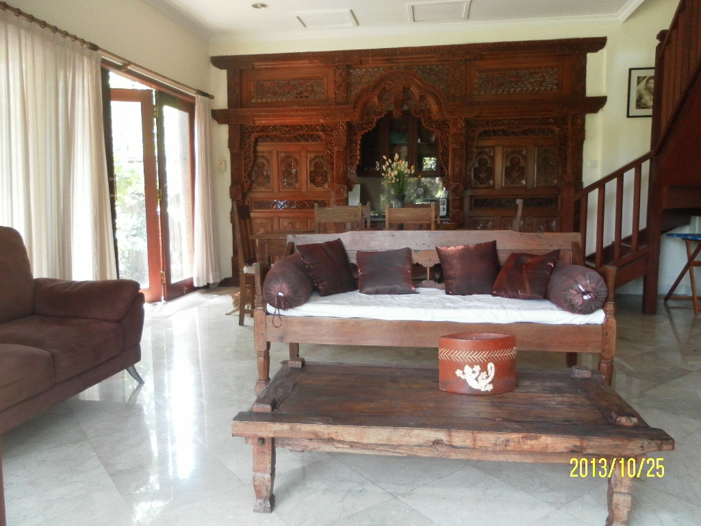 Authentic, hand carved, teak facade separates the kitchen and living area