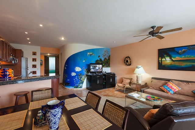 Large common area with dining table for six, flat-screen TV, and beautiful ocean mural