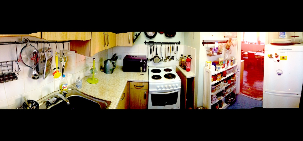 kitchen with breakfast bar, toaster, radio, washing maschine, microwave and cooker.