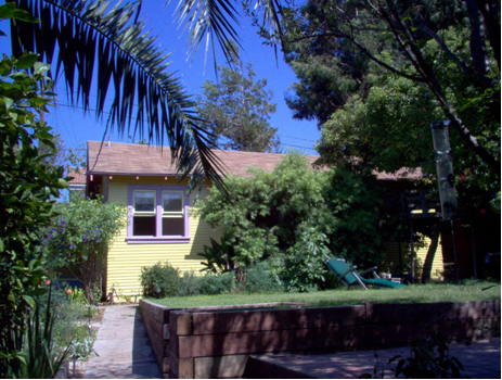Cottage and shared yard, from entry pathway, alongside main front house - Double windows in dining nook on the left, and entrance made private behind greenery in the middle.