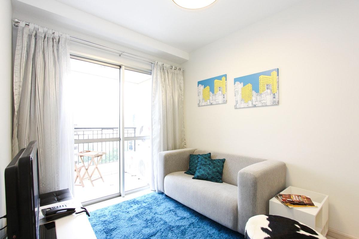 Sala de estar com ar-condicionado digital e TV de tela plana com canais a cabo.