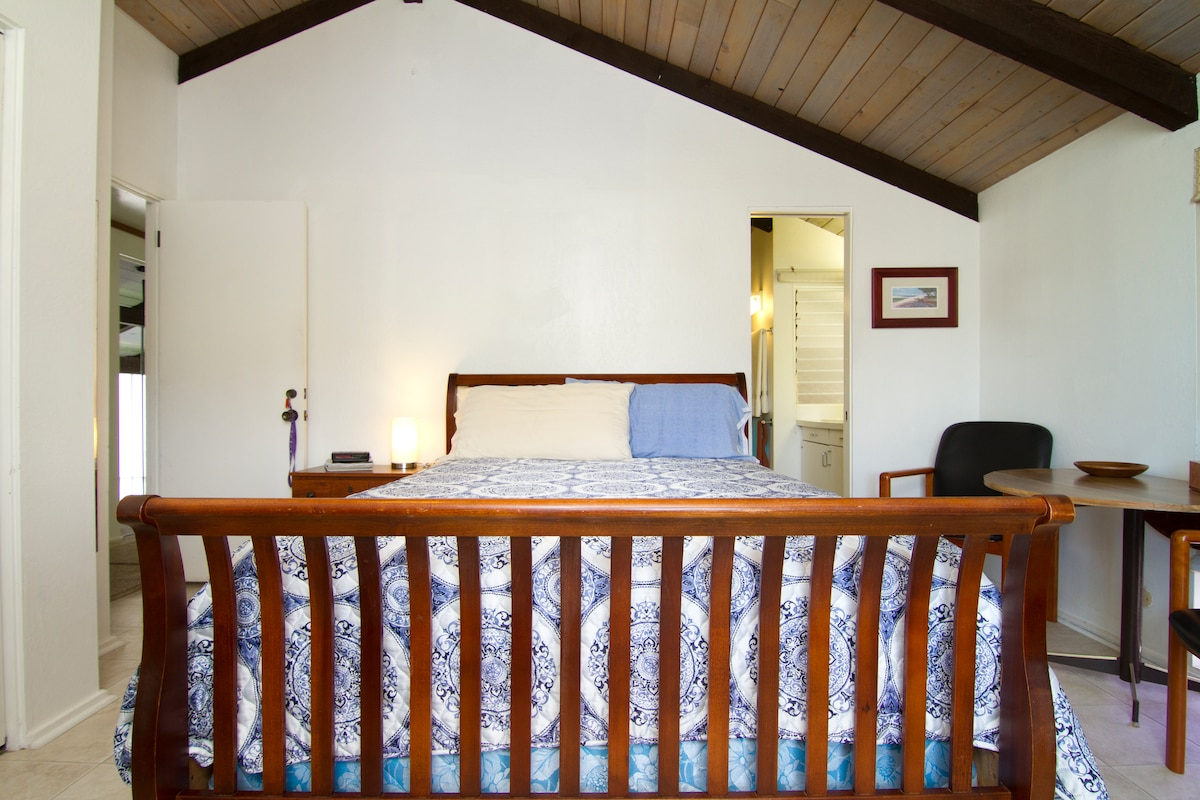 Balcony bedroom with queen bed.  Bathroom access seen here to right of bed.