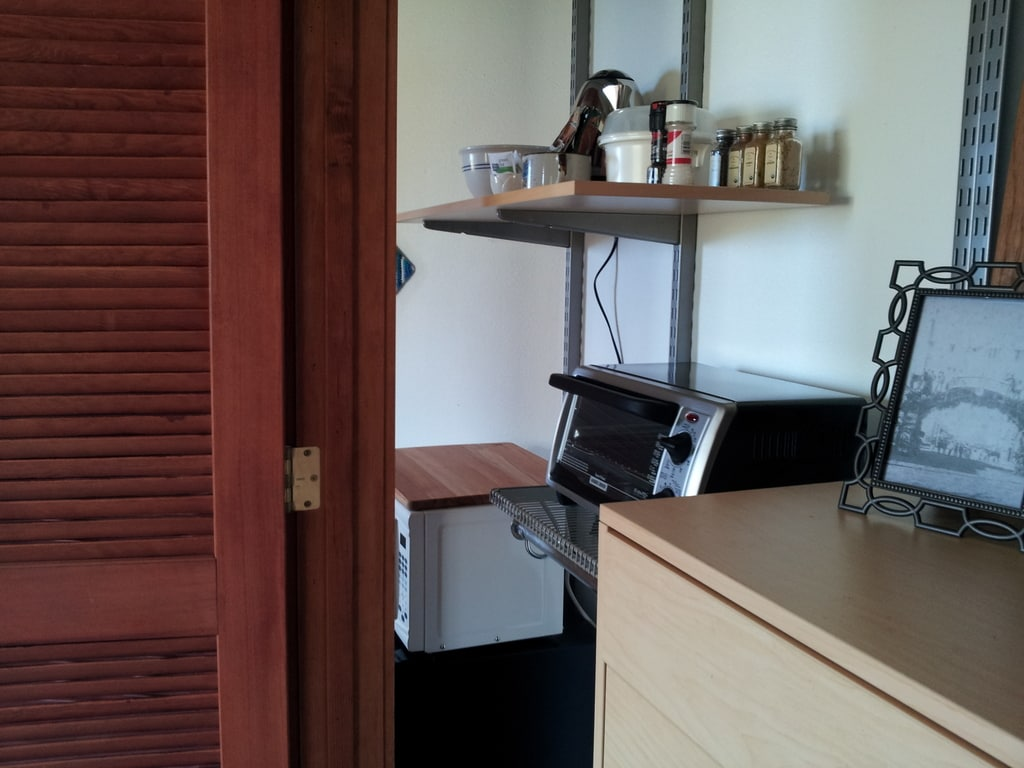 View of the kitchenette, from inside the clothes closet which also features a full dresser.