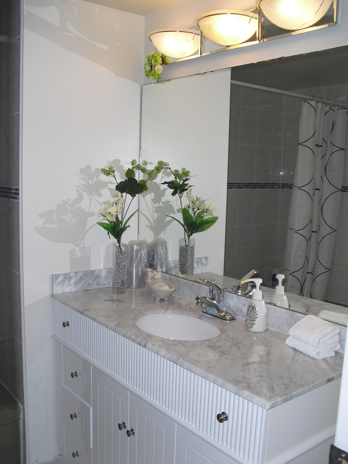 Private bathroom.  Beautiful marble counter top and large mirror in bright bathroom