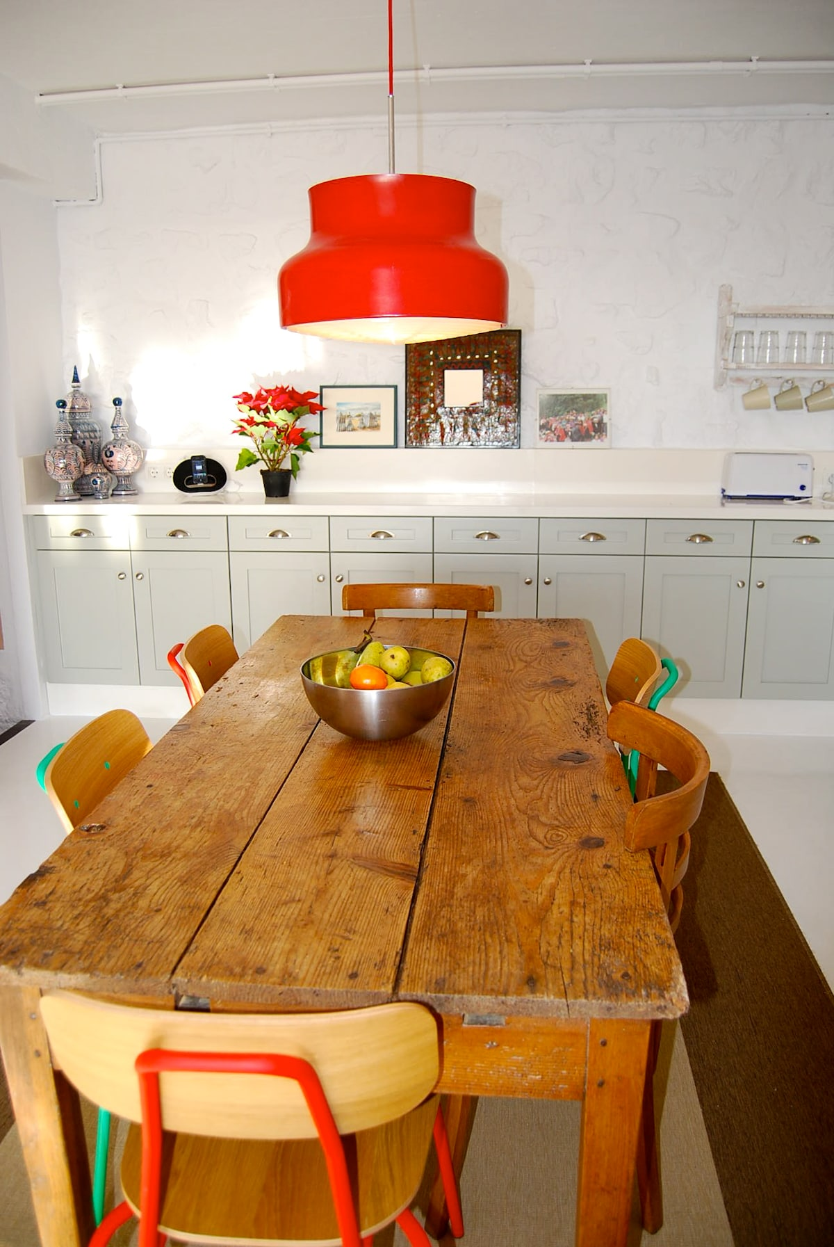 An old farm table and the red 50's lamp above create a relaxed mood