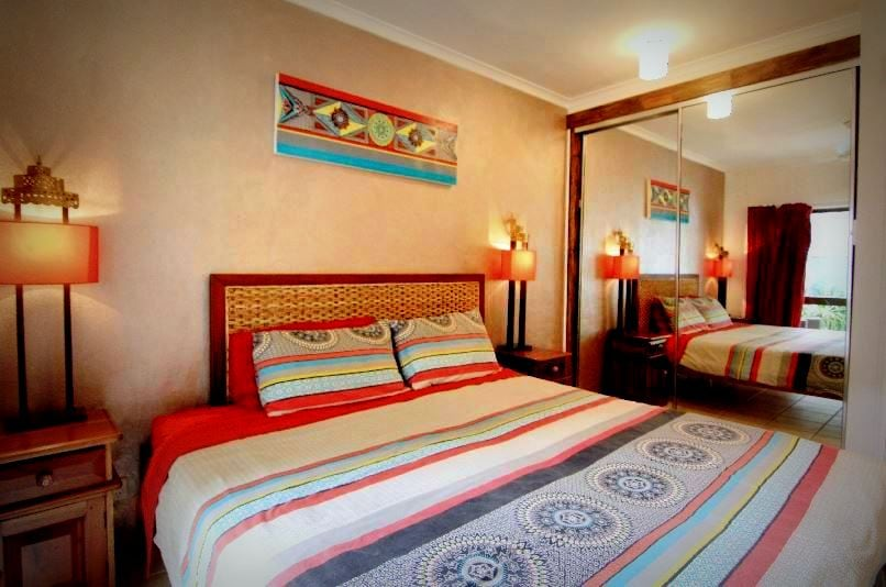 The main bedroom with king size bed and an outside courtyard area with seating  and en suite bathroom