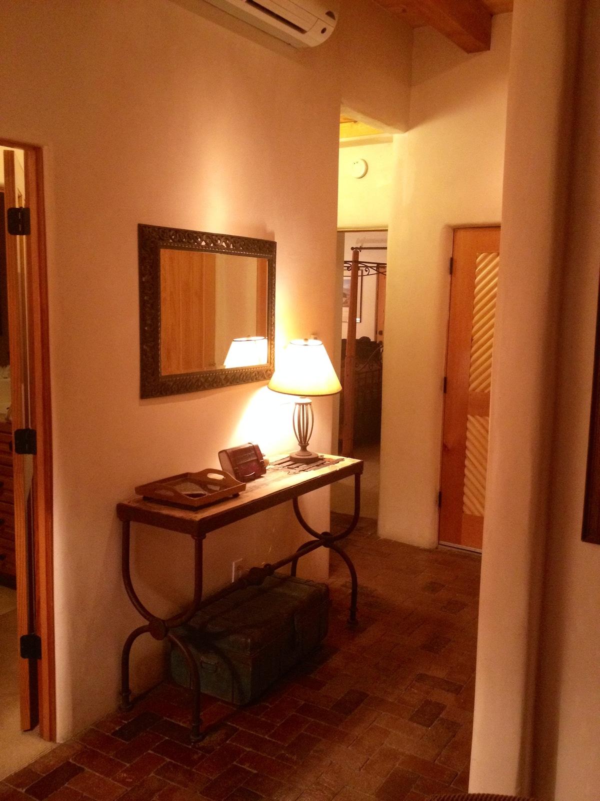Hall between bedrooms with guest book, air conditioner, and front door