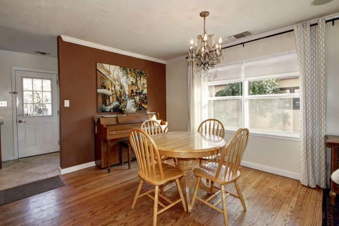 Dining room with table that has extra leaf. Piano in back ground.