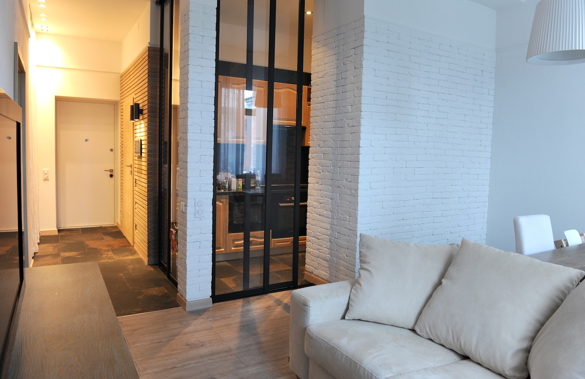Comfortable living room and a kitchen behind glass doors