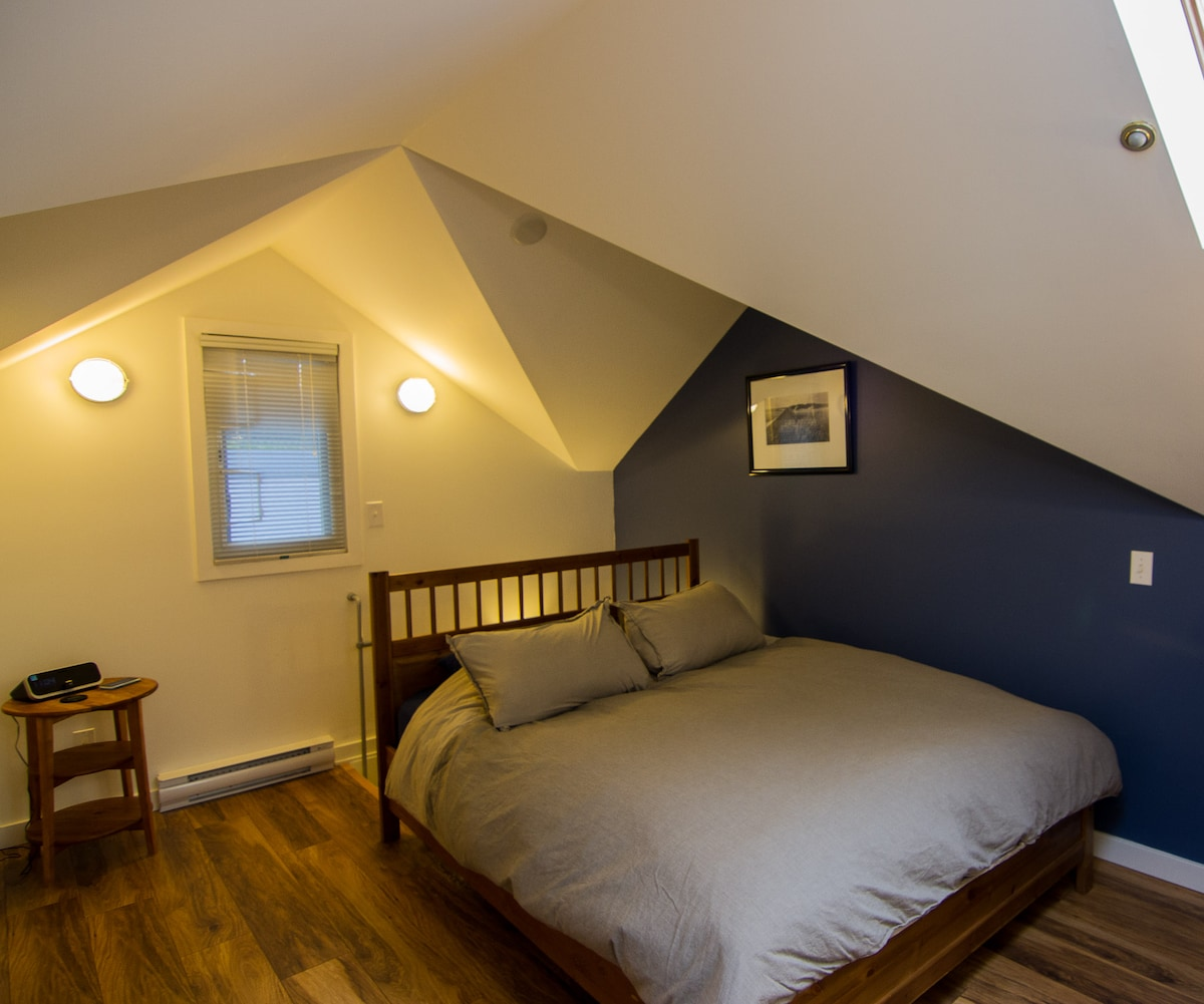 Cozy bedroom with lots of light coming in from the skylights.