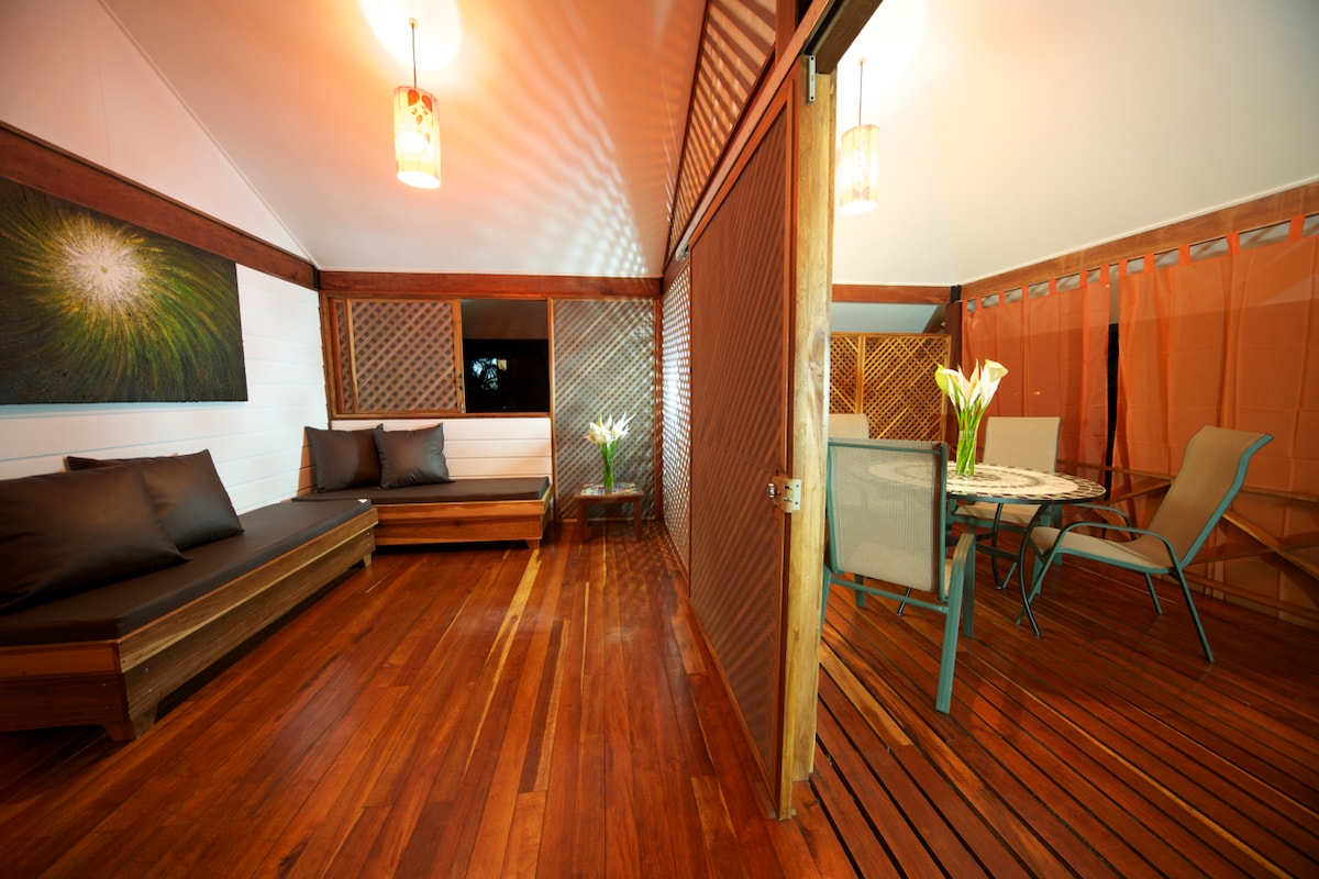 Living room with 2 sofas which can be adapted into 2 individual beds. Connected to porch with wooden sliding door with mosquito nets.