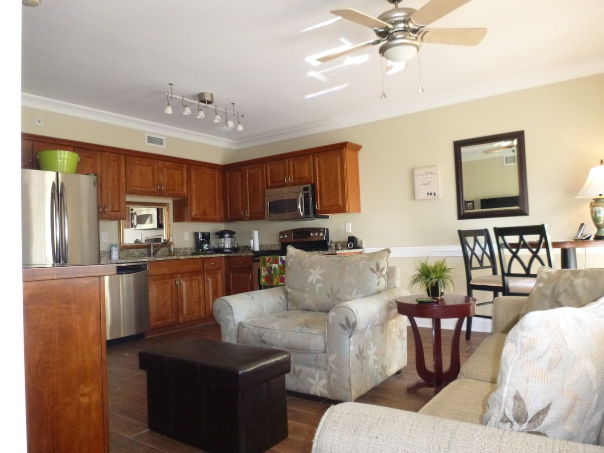 Den and fully furnished kitchen with stainless steel appliances and granite countertops.