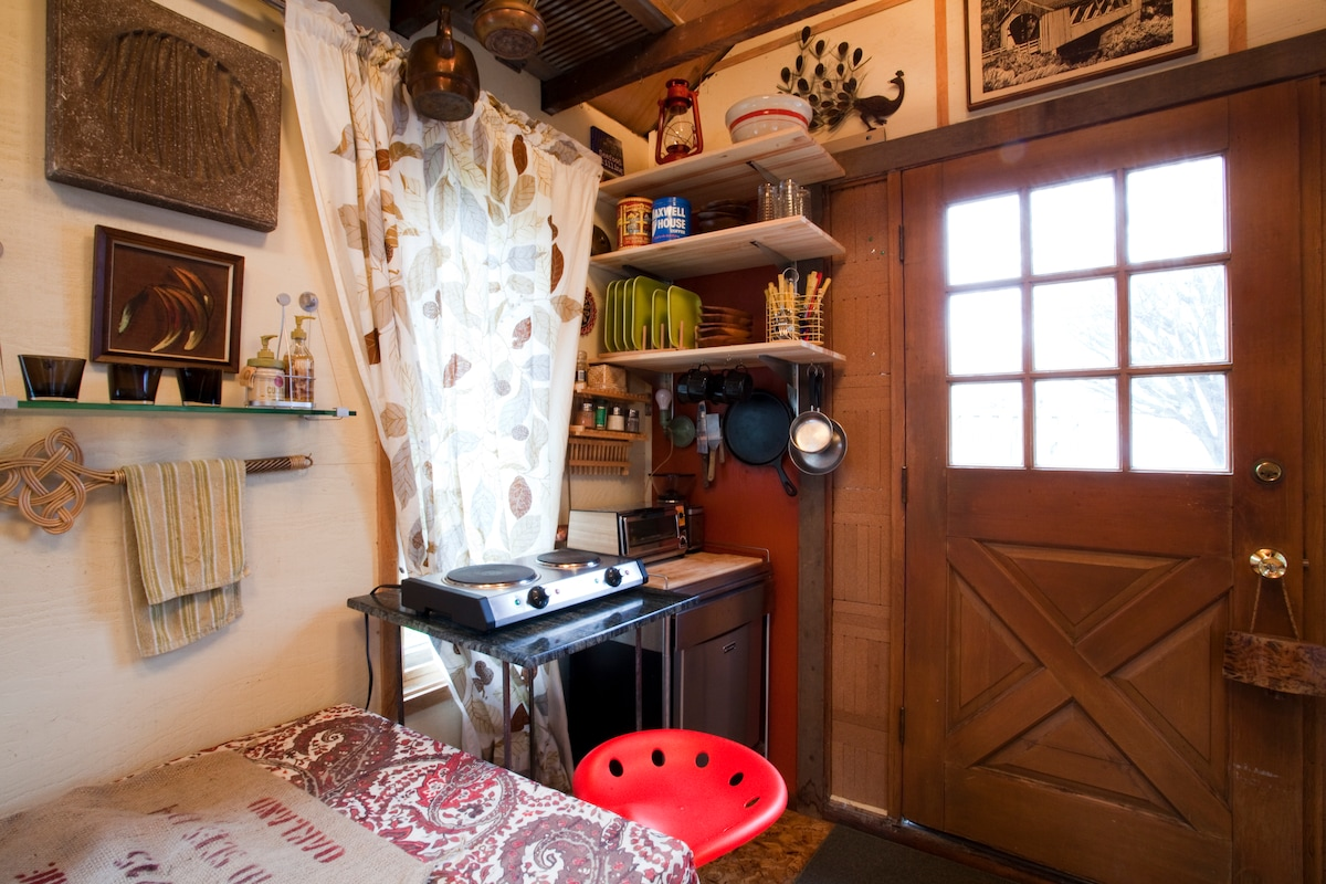 The little kitchen corner is equipped with a two-burner stove, a toaster oven, mini fridge, coffee grinder, a coffee press, some spices, and utensils.