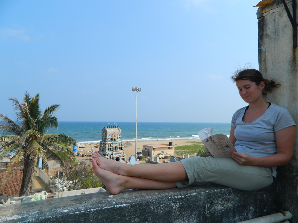Guest relaxing reading book at the terrace with beach backdrop.