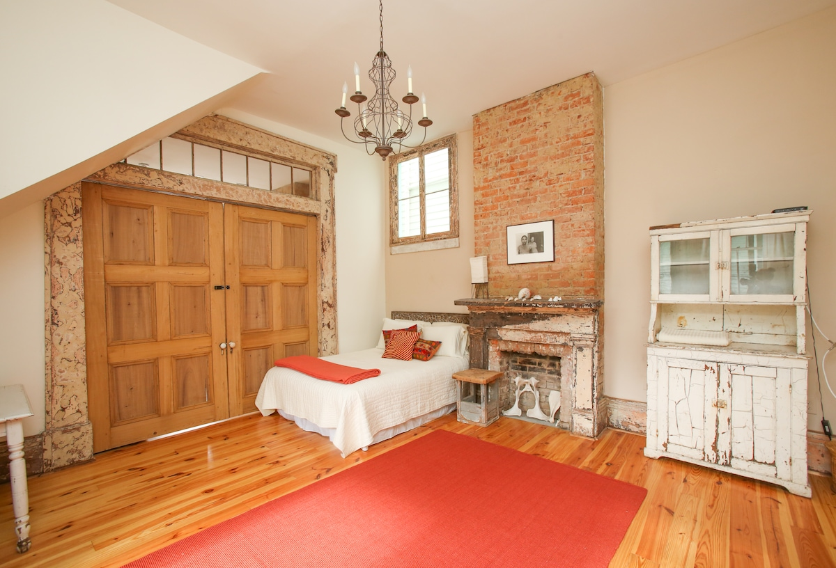 The front bedroom, airy and high-ceilinged, has its own French doors.