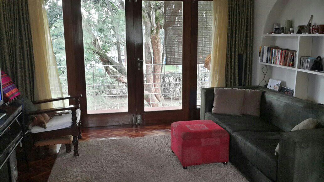 Living room area with French doors leading to the balcony overlooking the large garden with beautifully aged Jacaranda trees