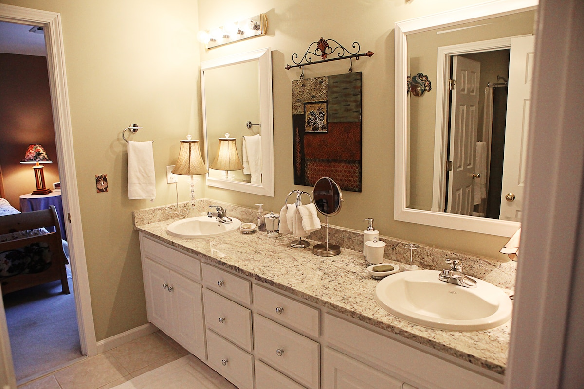 The updated shared bathroom features two sinks, is well-lit, and sports granite counter-tops.