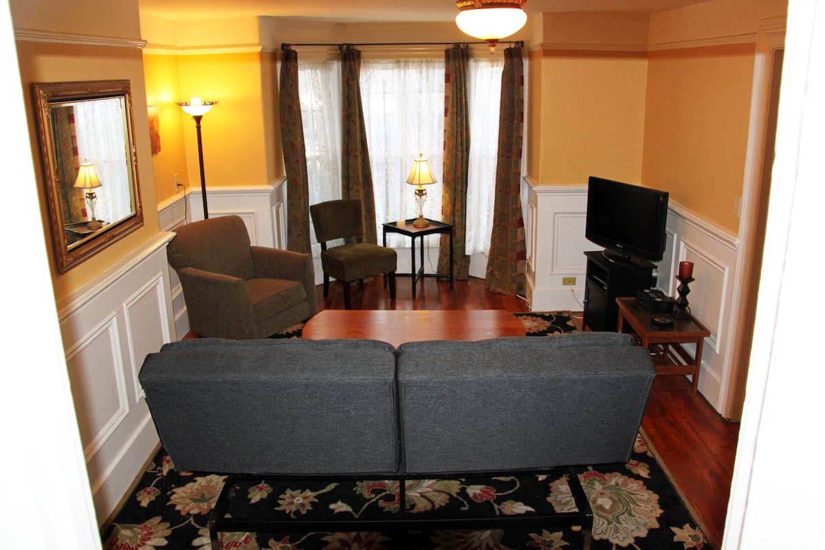 Large living room with bay window and flat-screen TV