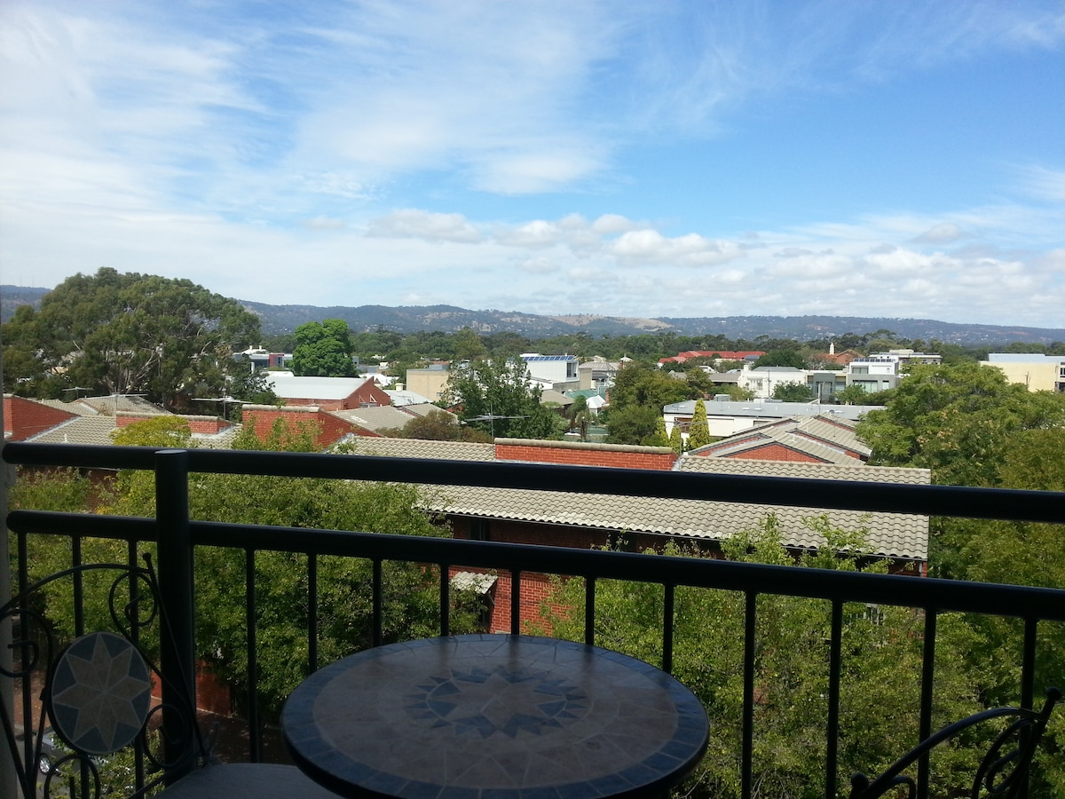Top floor views of Adelaide hills and sunsets, 10 minutes walk to City centre, tram and Chinatown.