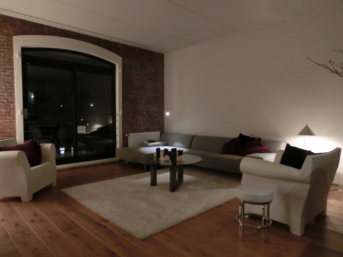 Spacious living room, TV, DVD and stereo, big window looking out on Rotterdam
