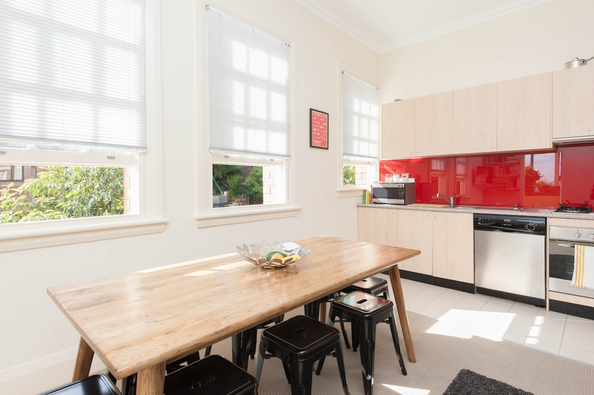 Dining table and kitchen overlooking the beautiful Bourke Street (famous tree- and cycleway-lined street in Sydney)