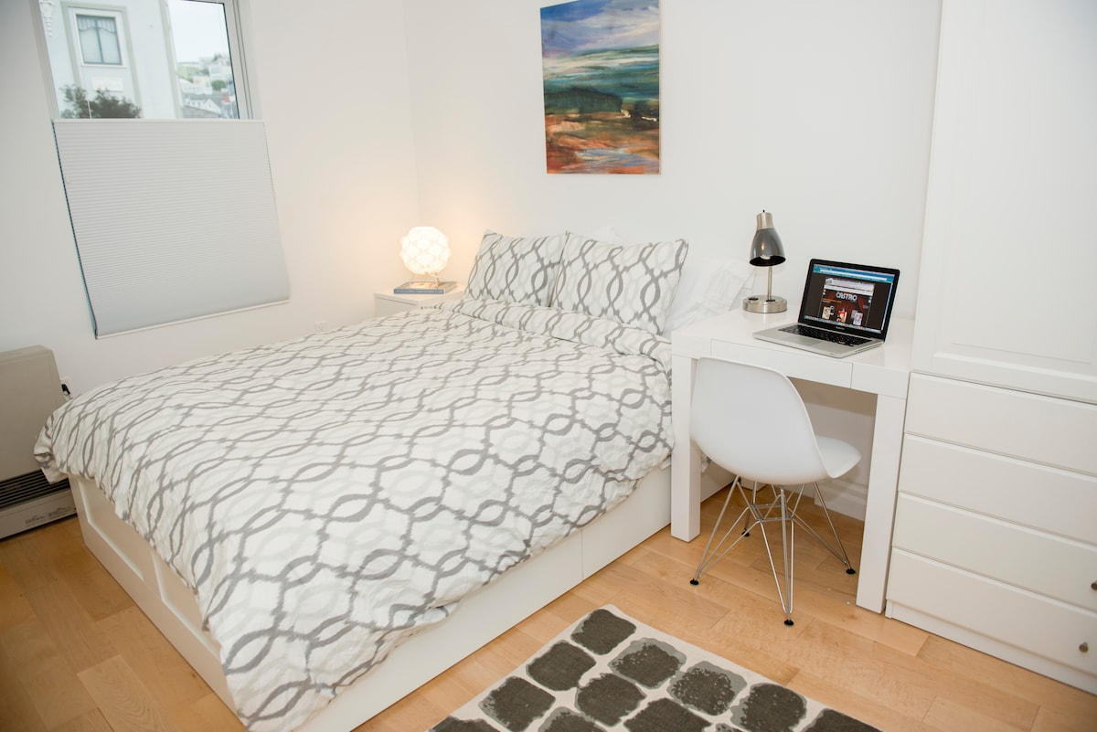 Bedroom has a queen size bed with storage drawers, nightstand, desk and wardrobe.