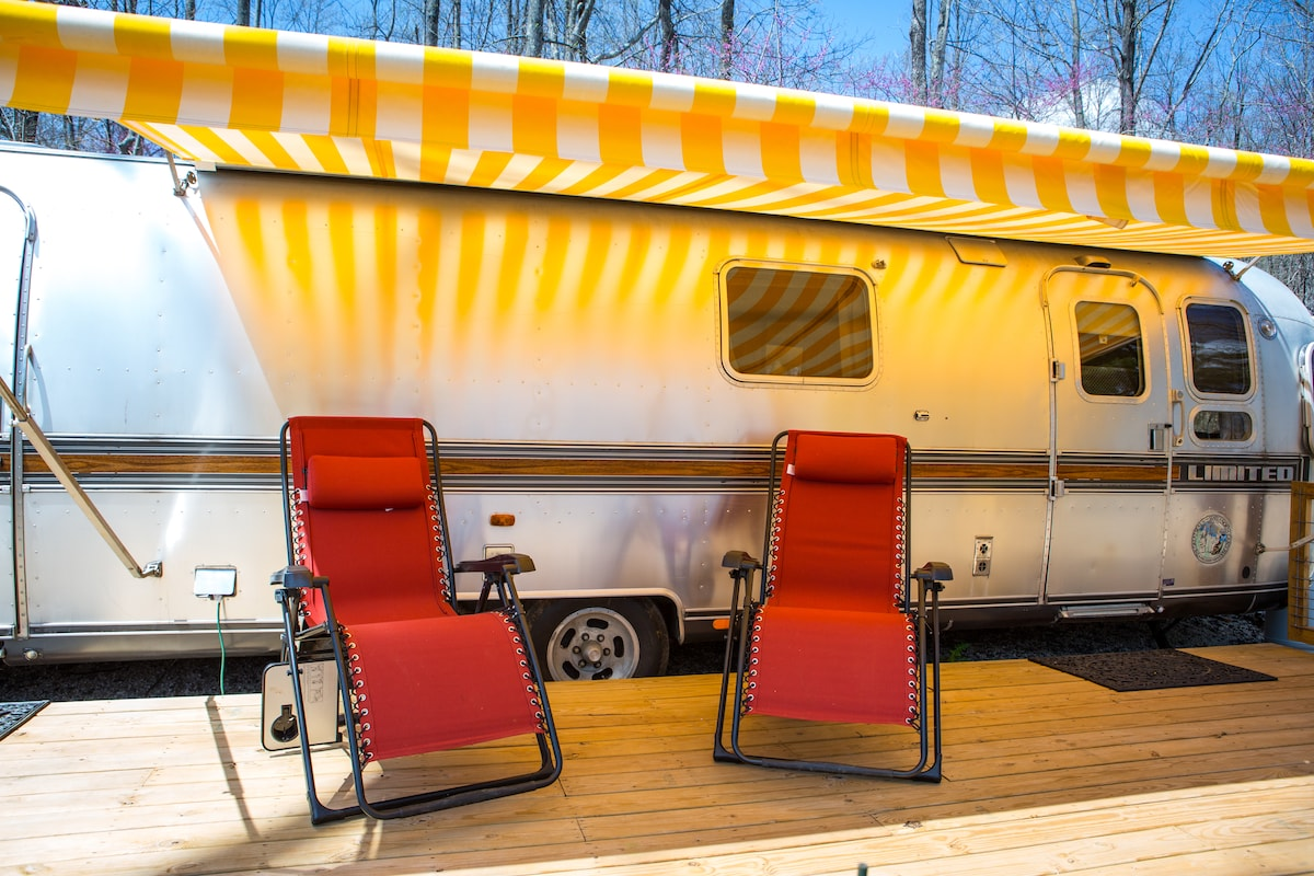 Meet the Dawn Treader, our vintage Airstream. Lounge chairs under the awning await you.