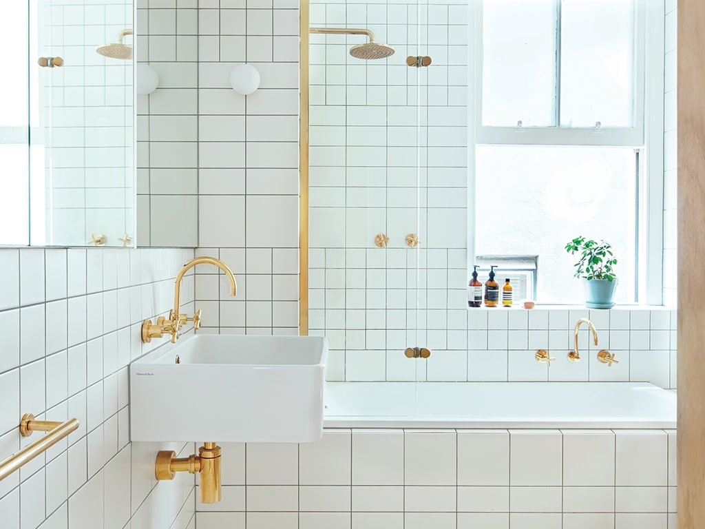 Pristine white bathroom with gold taps. Features shower, deep bath, washer and dryer.