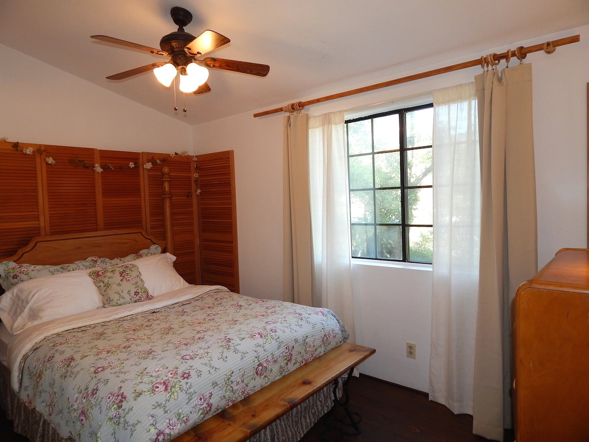 Second upstairs bedroom has a queen bed, wood floors, vaulted ceiling, ceiling fan and large window. Blackout curtain for late sleepers.