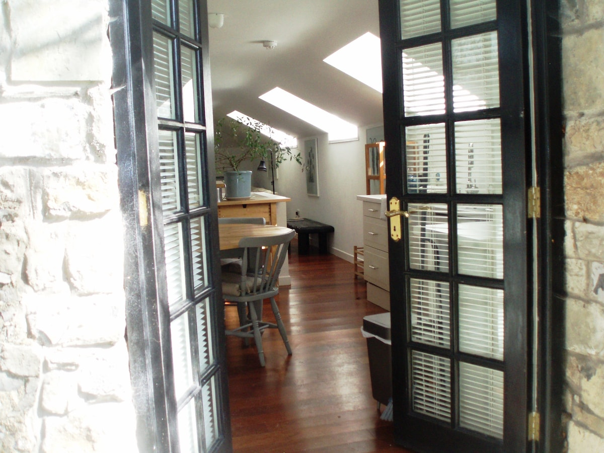 """Entrance to the Mews from the patio area showing the """"loft living""""  kitchen /dining area with the sitting space beyond."""