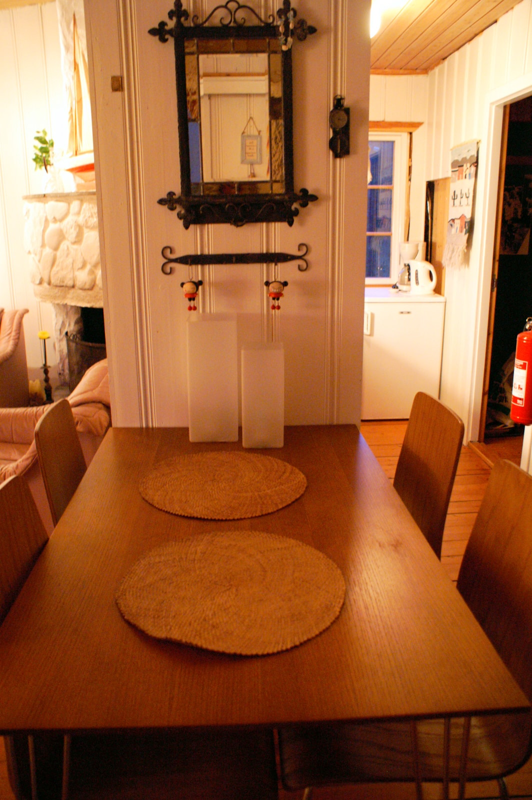 Dining table, fireplace to the left, kitchen to the right.