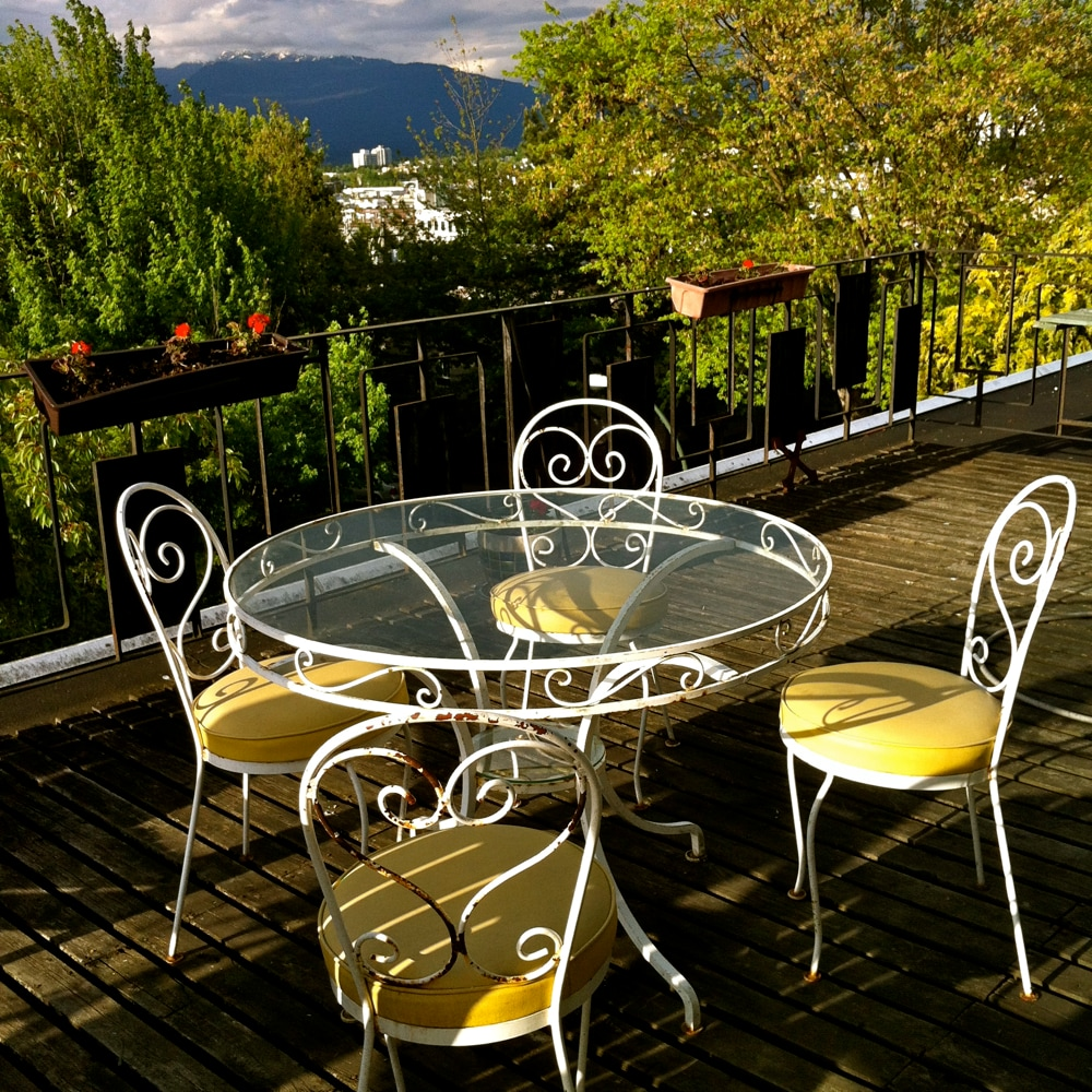 Patio table in the afternoon sun, northeast view of trees and mountains in the distance.
