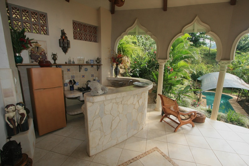 enjoy cooking and dining as you overlook your pool and lush gardens