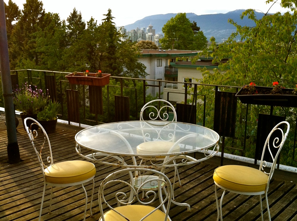 Lovely patio table to enjoy breakfast, lunch, dinner,  afternoon tea or sunset cocktails.  View looking northwest at downtown Vancouver and North Shore mountains.
