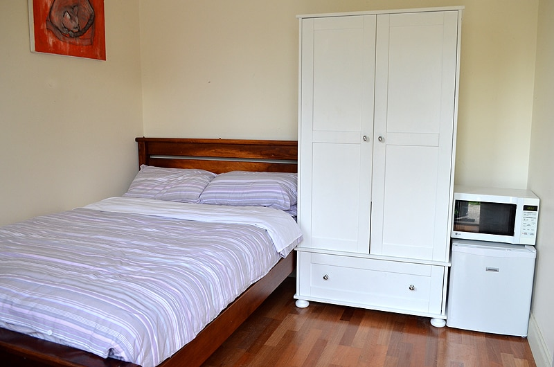 Tastefully furnished room with teak bed and fridge -a complete home