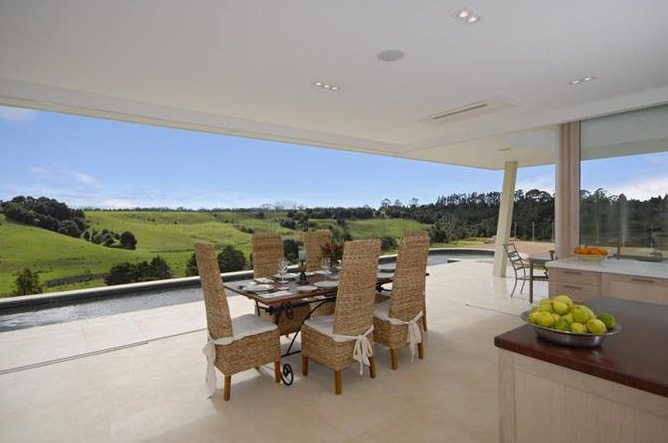 Open air breakfast seating shown with large ranch sliders open.