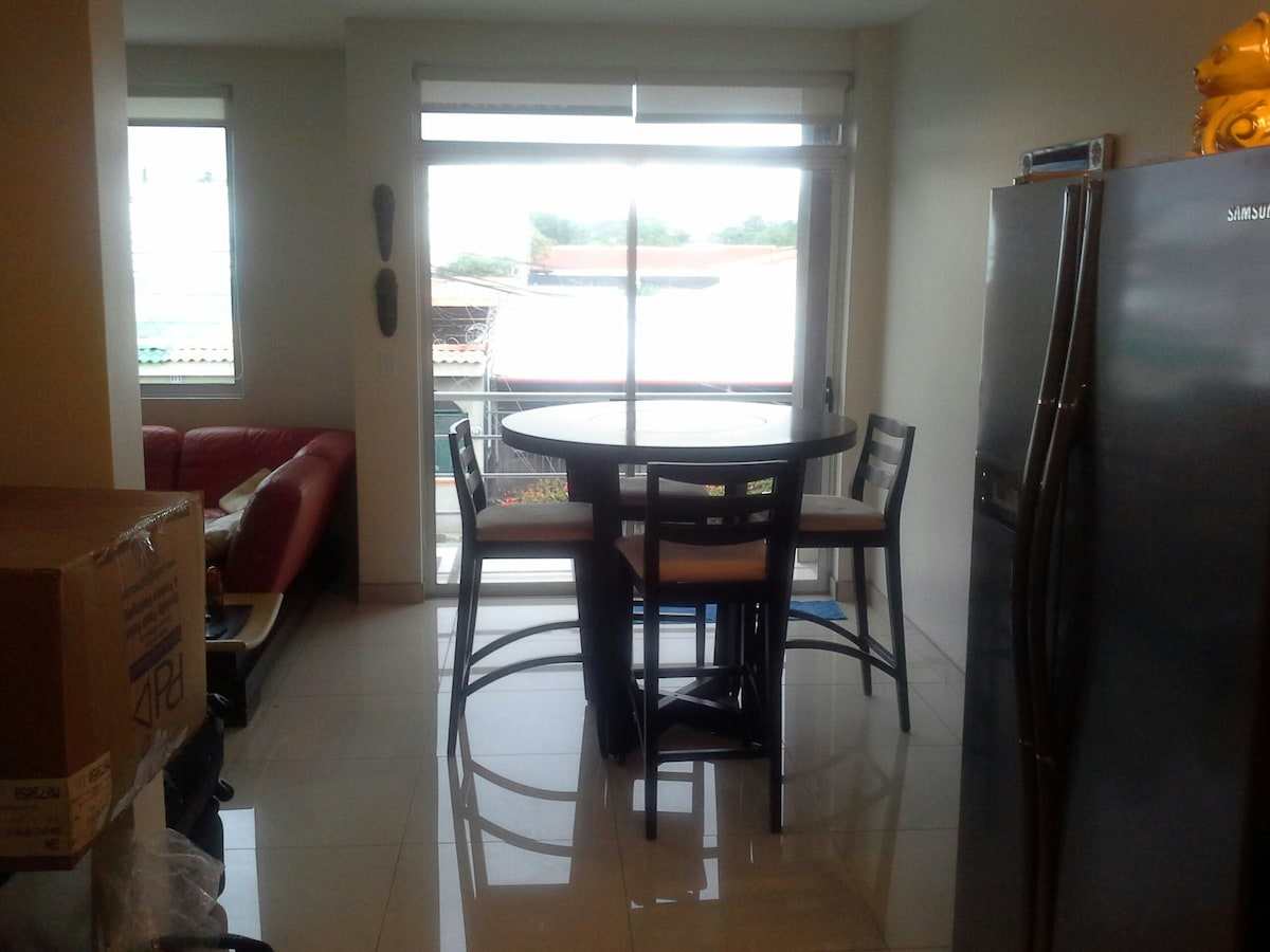 view from kitchen.  you can see the sliding glass door that leads onto balcony, and on left is living room.