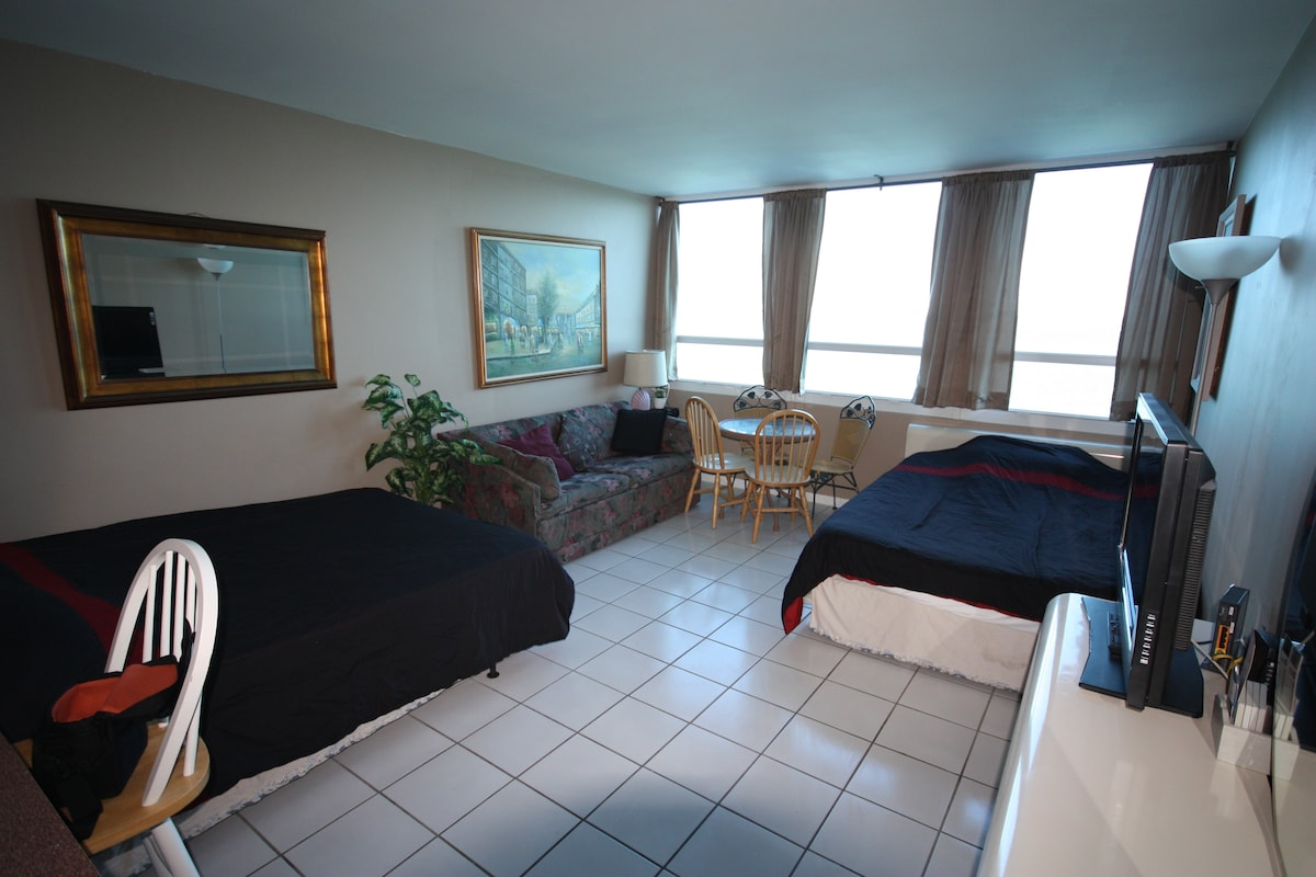 Inside the Apt, 2 Queen Beds and a Small Couch, plus dining table with 4 chairs