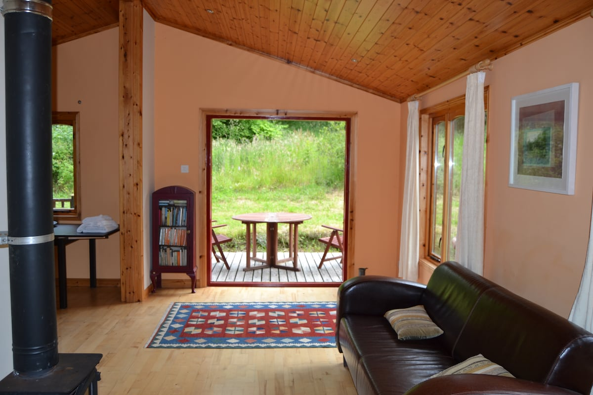 Living room with double doors open onto deck with picnic furniture