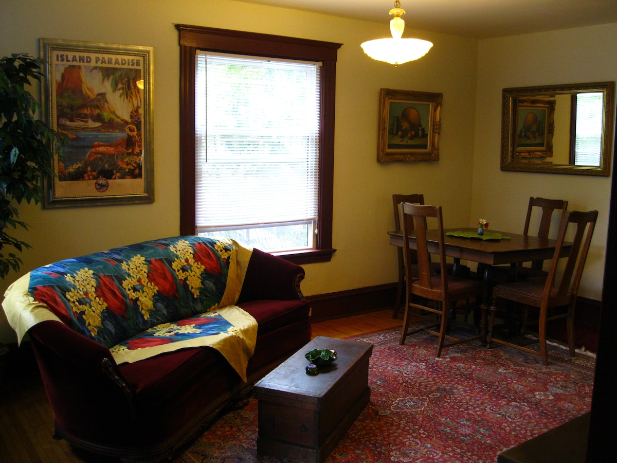 Bright living room furnished with couch, expandable dining table, AC, flat screen T.V./DVD with a selection of movies, a local rental place one block away plus our own large inventory :)
