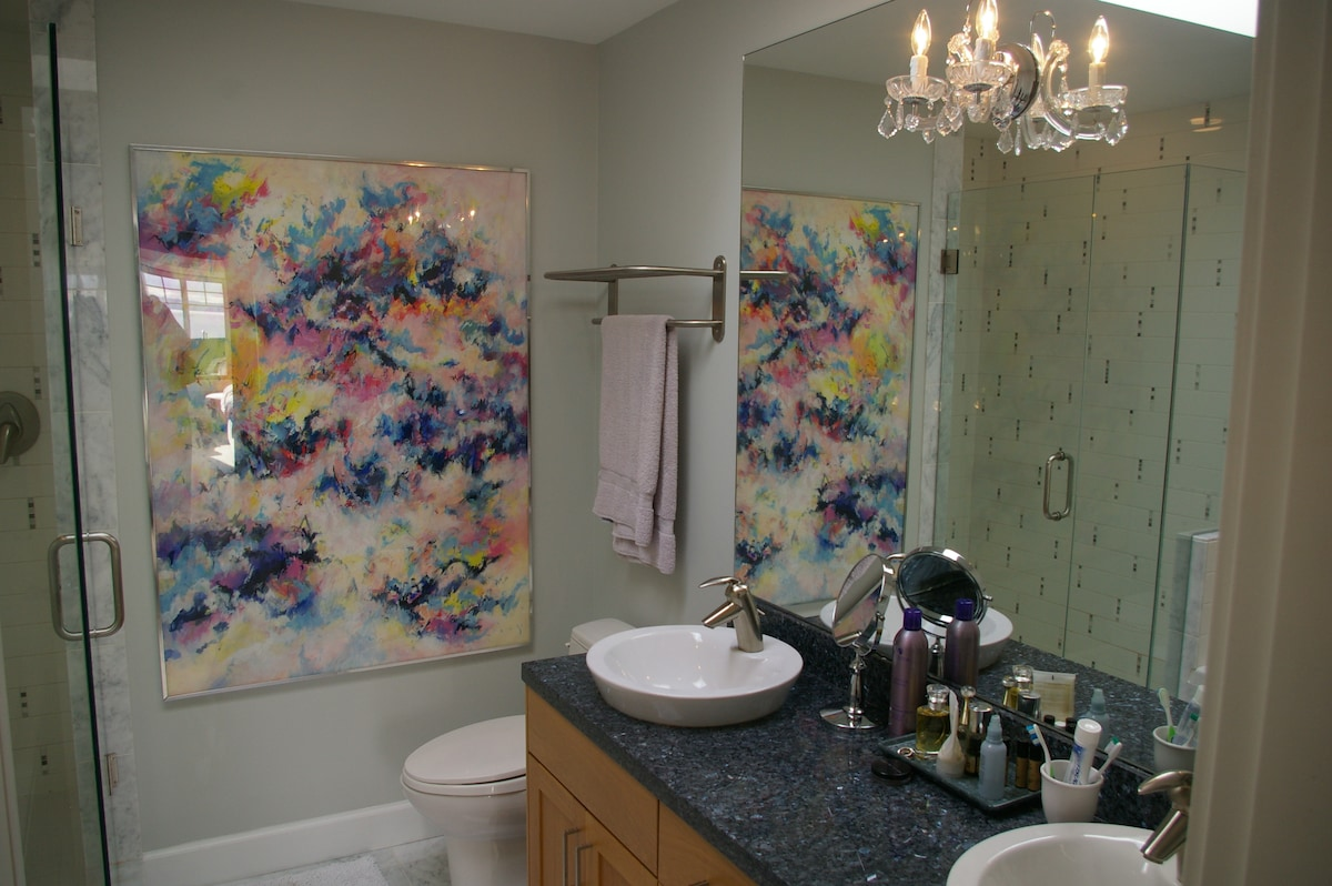 The master ensuite with double sink vanity, soaker  tub and four nozzle shower
