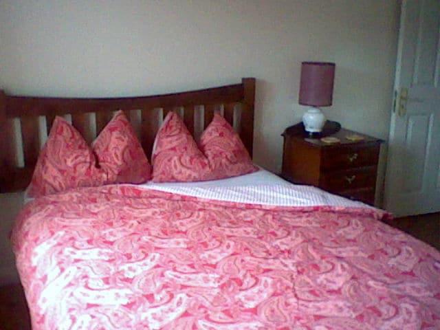 Double bedroom with wooden floor, WC/shower en suite.