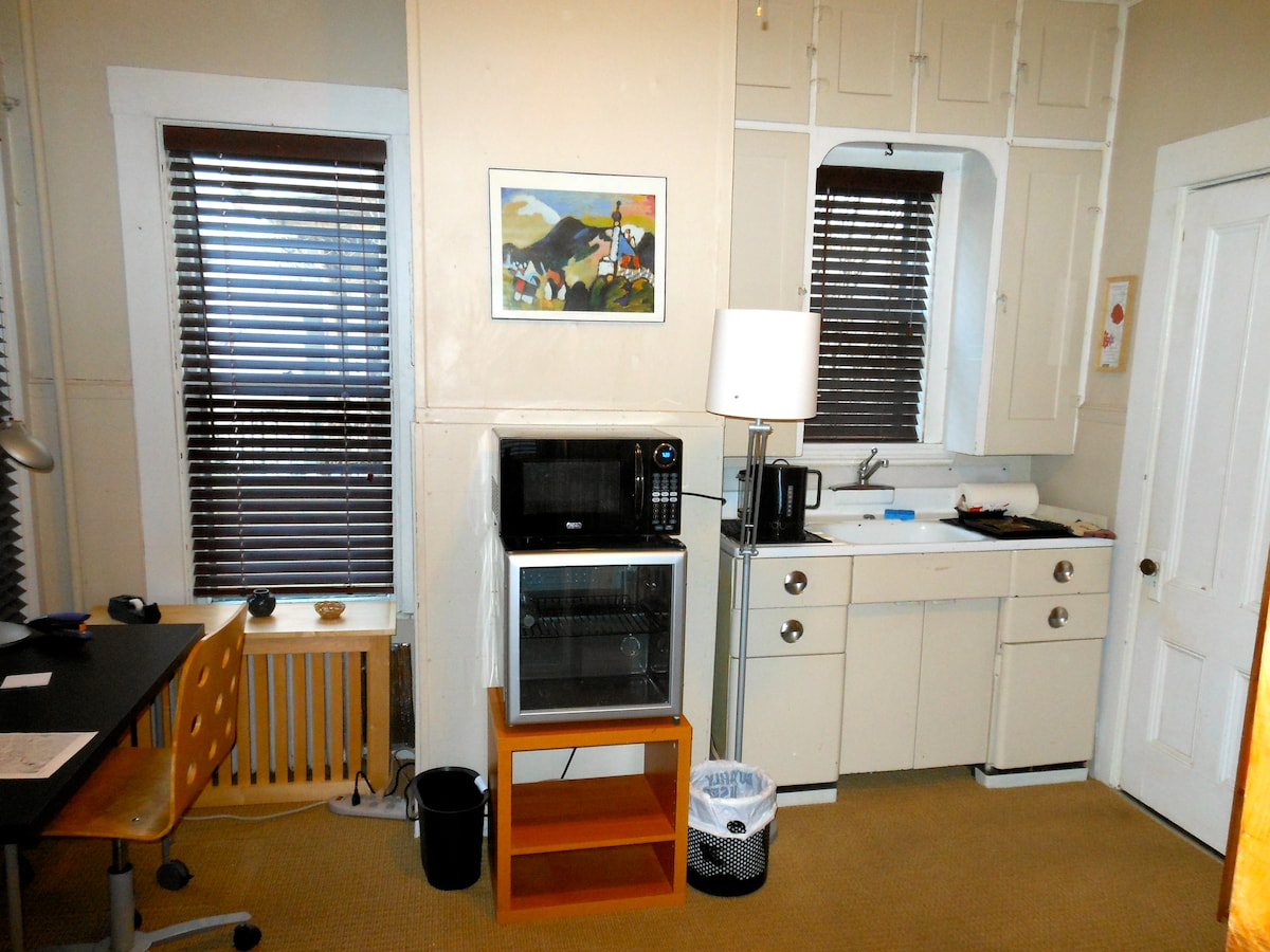 Kitchenette with small fridge and microwave, coffee maker