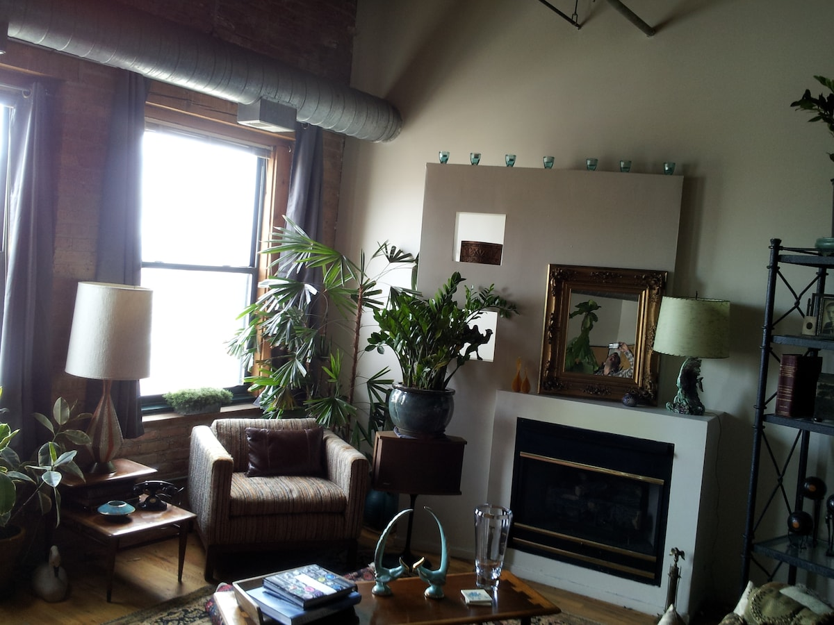 This is a partial view of the loft living room which has 14 ft. ceilings, Hard wood floors with oriental rugs. All furnished with mid century modern furniture and some select pieces from the mid 19th century.  There is a gas fireplace for the cool nights