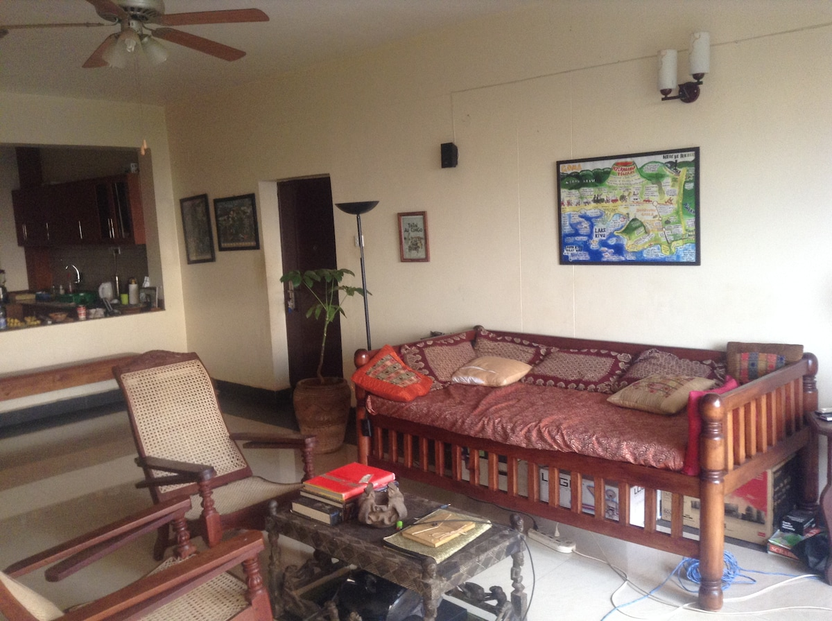 The living room is decorated with Swahili furniture, art from the region, stereo, and a small desk by the balcony.