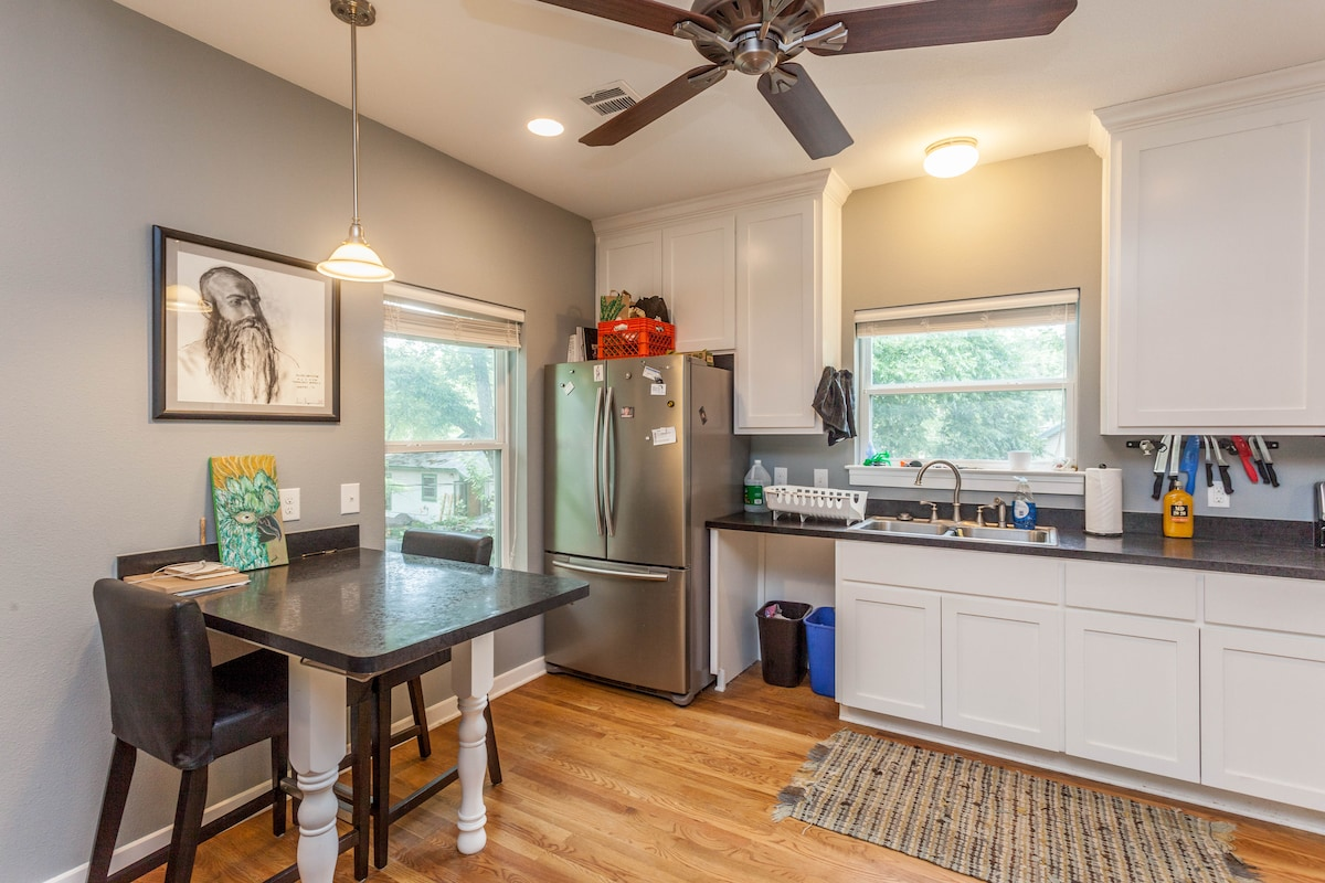 Full kitchen with fridge, oven, stove, microwave, silverware and dishware.