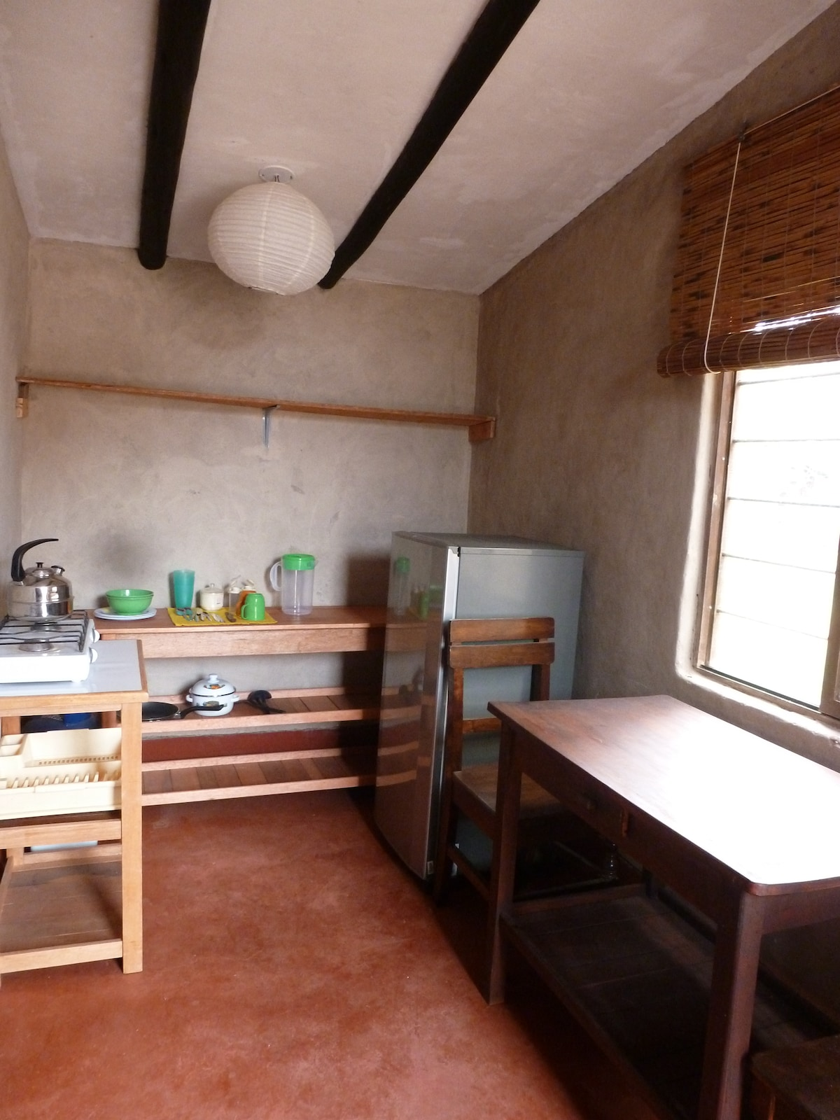 Small mini-kitchen with refrigerator, two burner gas stove top, basic cooking & eating utensils and equipment.